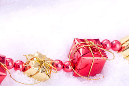 christamas: red and golden gift boxes with christamas ball on snow