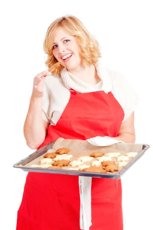 blond woman with red apron present christmas cookies on a  baking tray photo