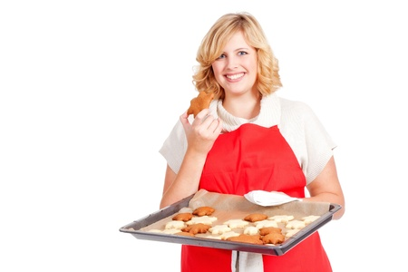 christmas baker's: blond woman with red apron present christmas cookies on a  baking tray Stock Photo