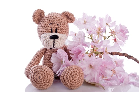 brown stuffed animal teddy bear with pink blossom Imagens
