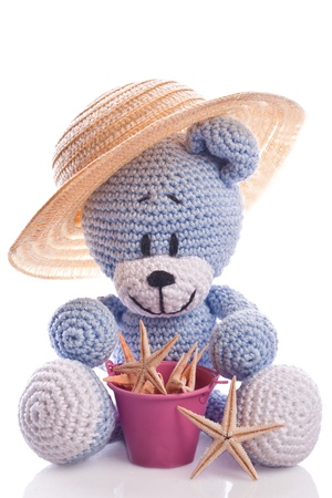 teddy bear with hat and  pink basket on the beach Imagens