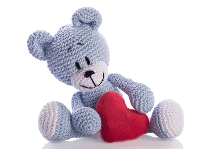 blue knitted teddy bear with red heart Stock Photo