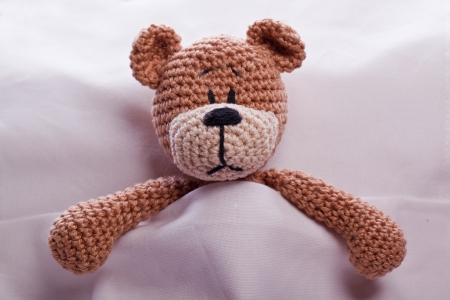 sick teddy bear: brown teddy bear lyiing sick in bed