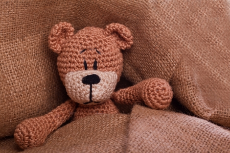 brown teddy bear lyiing sick in bed photo