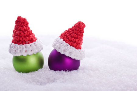 green and pink christmas ball decoration with santa hat in snow photo