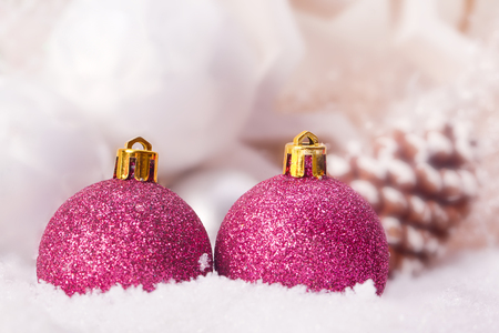 pink christmas bauble decoration with fir cone in snow