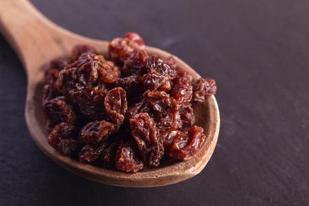 raw raisin on wooden spoon as baking ingredient