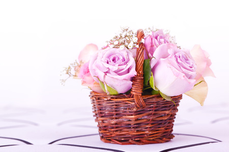 pink roses in brown basket of withe