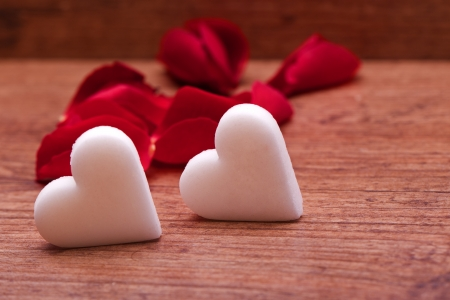 one heart on wooden background with  rose petals