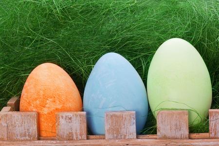 three eggs sit on wooden fance photo
