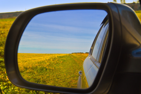 View through a car mirror. Blue and Yellow reflection in mirror. Ukrainian rural landscape