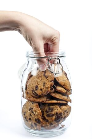 Een hand nemen van cookies van een glazen pot op witte achtergrond