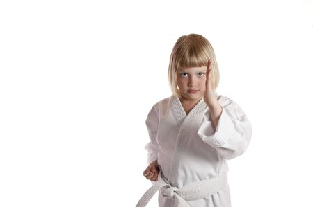 Cute girl in karate dress with guard up on white background