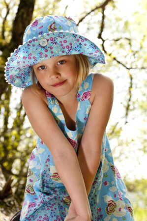 Cute child in blue summer dress in the woods
