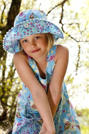 Schattig kind in de blauwe zomer jurk in het bos