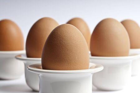 Zes bruine eieren in ei kopjes Stockfoto