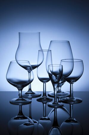 Six glasses on glass surface backlit with blue gelled flash.  Stock Photo