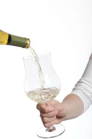 Gieten witte wijn in glas bedrijf in hand op witte achtergrond