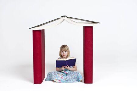 Een kind meisje het lezen van een boek in een huis gebouwd van boeken Stockfoto