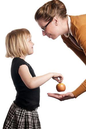 Schoolchild gives teacher apple on white background Stock Photo - 4956020