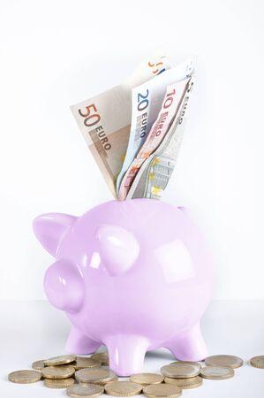 Een spaarvarken met euro biljetten en euromunten op witte achtergrond Stockfoto