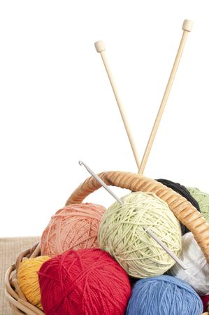 Different colored yarn in basket with knitting needle and crochet hook