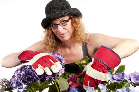 Attractive woman does gardening with secateurs on white background