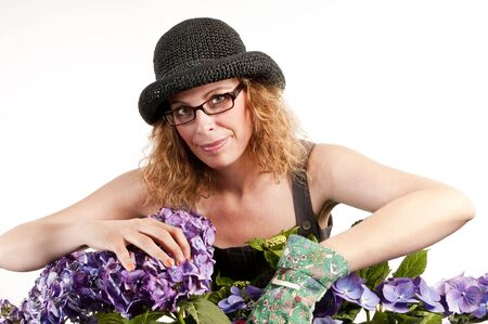 Attractive woman does gardening wearing a hat on white background
