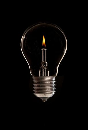 A light-bulb with candle flame inside Stock Photo
