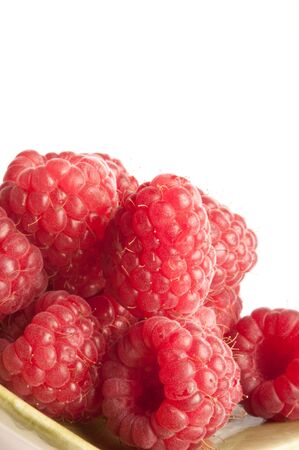 Raspberries on green dish isolated on white background
