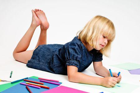 Grappig meisje tekent met de pennen op de witte achtergrond