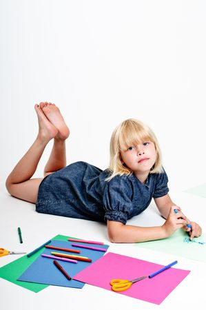 Young cute girl draws with pens on white background