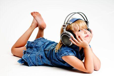 Jong meisje naar muziek luisteren in de hoofdtelefoon op witte achtergrond Stockfoto