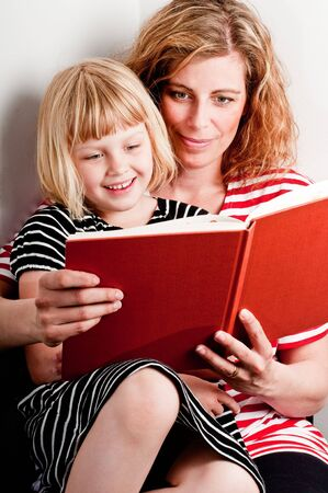 Een moeder is een boek te lezen aan haar dochter Stockfoto