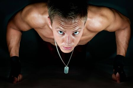 Muscular male kickboxer doing push-up on his knuckles