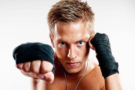 Close up on male kickboxer punshing isoleted on white background Stock Photo