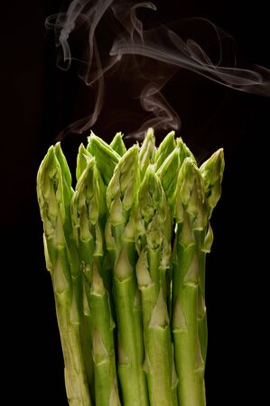 asparagus bunch with steam on black background Stock Photo