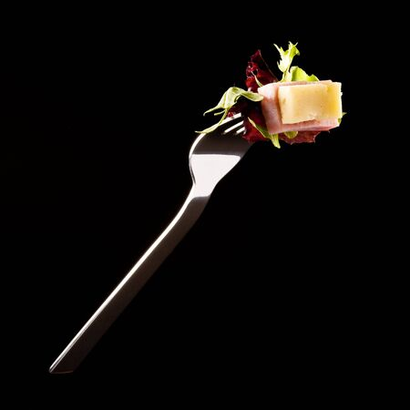 sallad: Ham and cheese sallad on a fork isolated on black