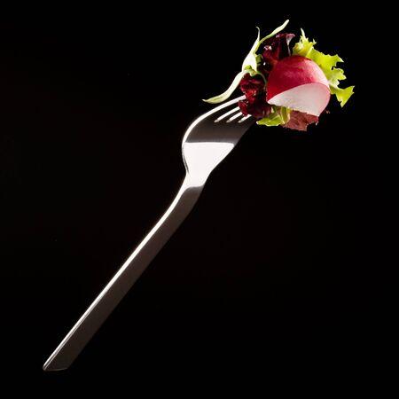 Radish and salad on a fork isolated on black