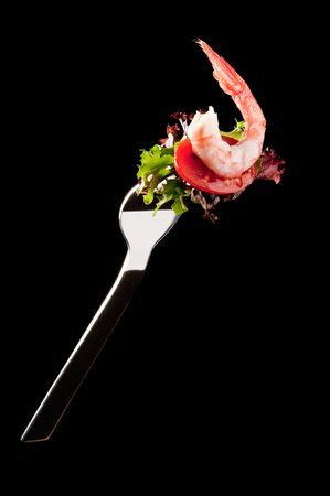 Shrimp salad on a fork isolated on black