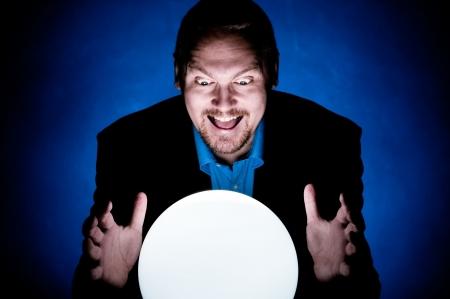 adivino: Un hombre de negocios, mirando hacia el futuro en una bola de cristal