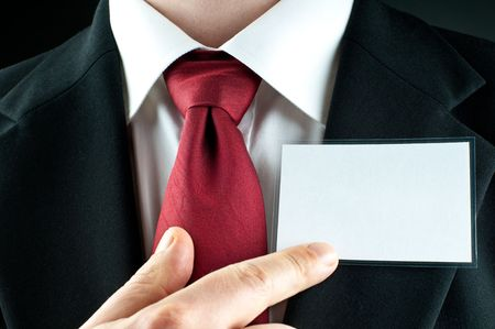 A businessman with a tie points on a blank nametag