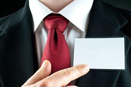 Een zakenman met een stropdas punten op een lege naamplaatje