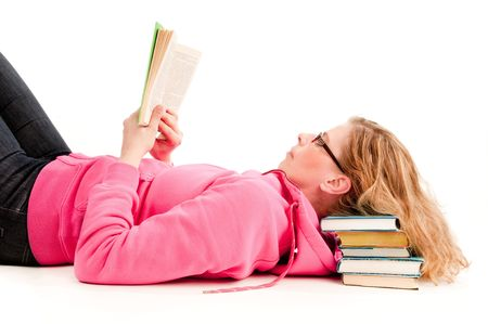 A woman reads a book resting head om pile of books