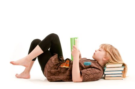 A girl reads a book resting head om pile of books