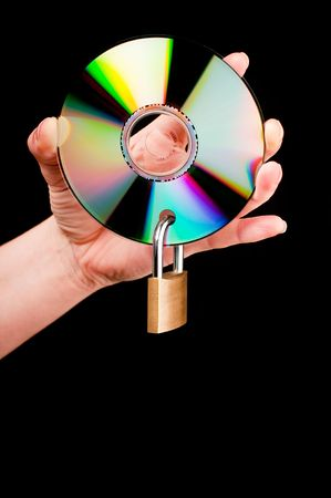 Een hand die een CD met een hang slot op zwarte achtergrond Stockfoto