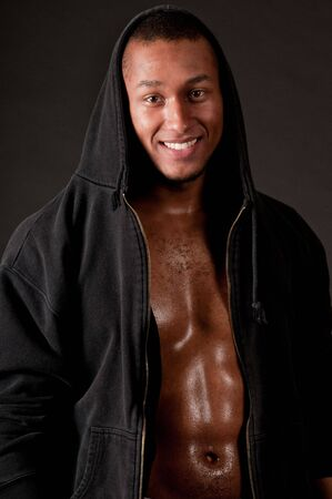 Young muscular male in hood on black background Stock Photo
