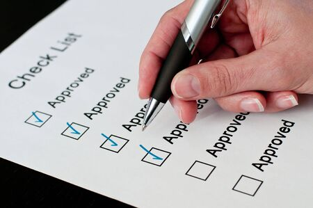Female hand approving on checklist