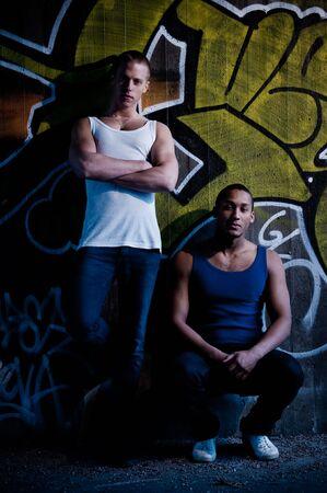 Twee jonge mannelijke modellen op graffiti achtergrond met grungy look