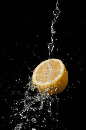 Water splashing on lemon on black background